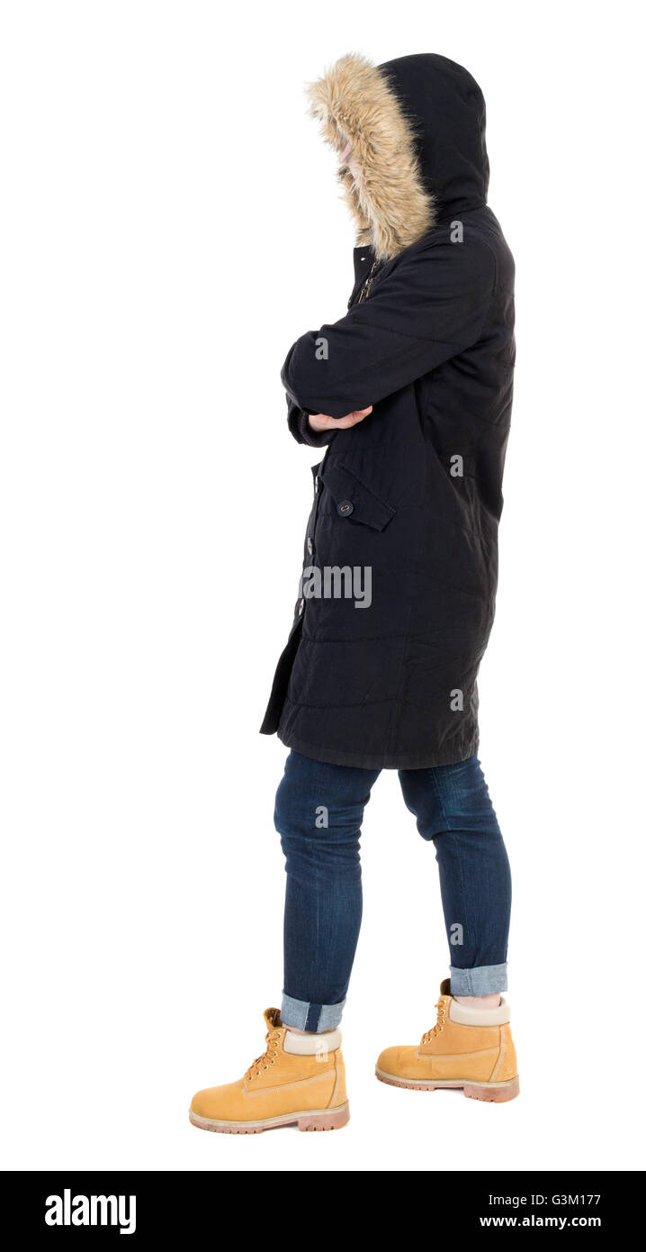 Back view woman in winter jacket looking up. Standing young girl in parka. Rear view people collection. backside - Stock Image