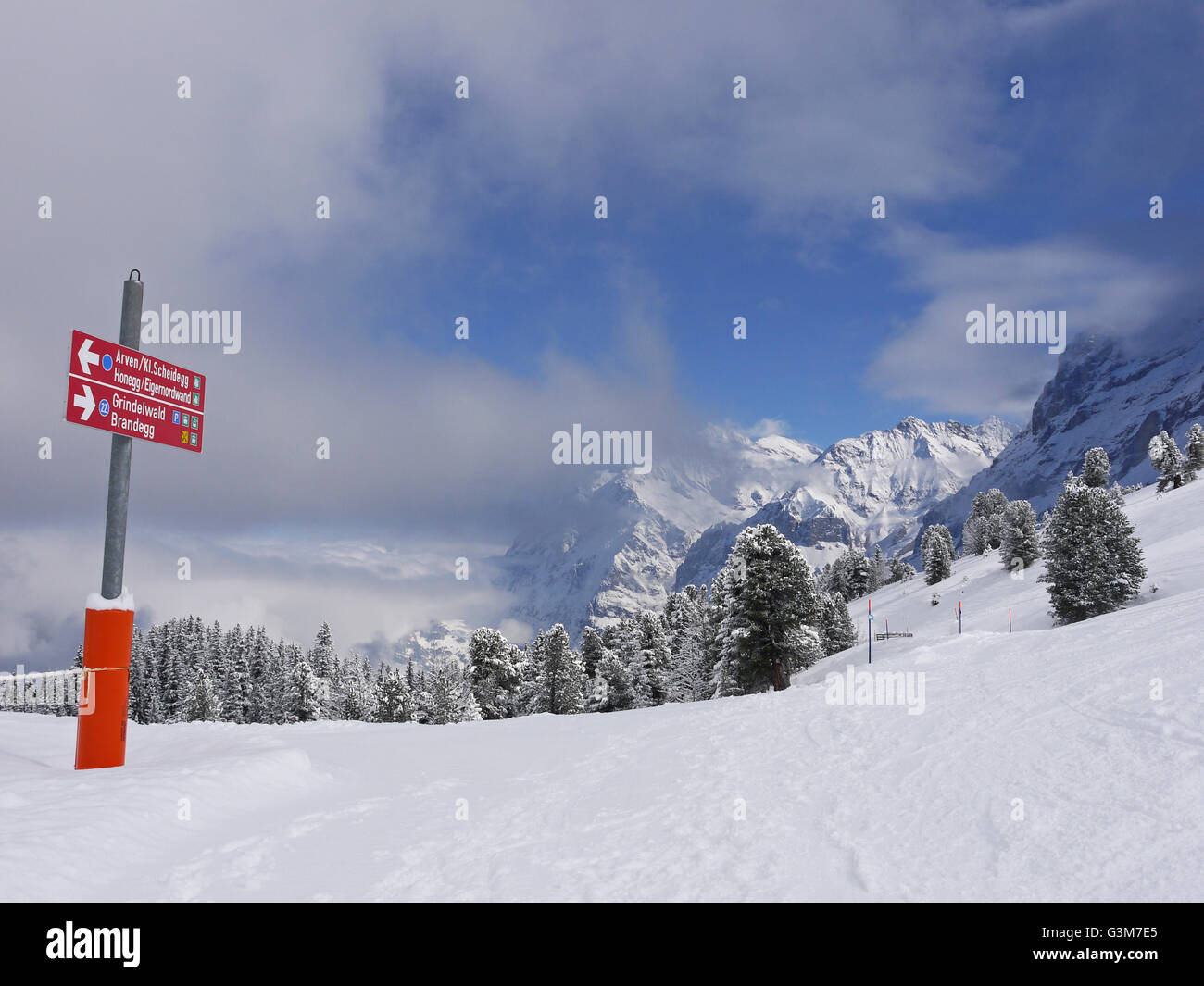 Sign post on the ski piste from Kleine Scheidegg to Grindlewald with the Wetterhorn in the background - Stock Image