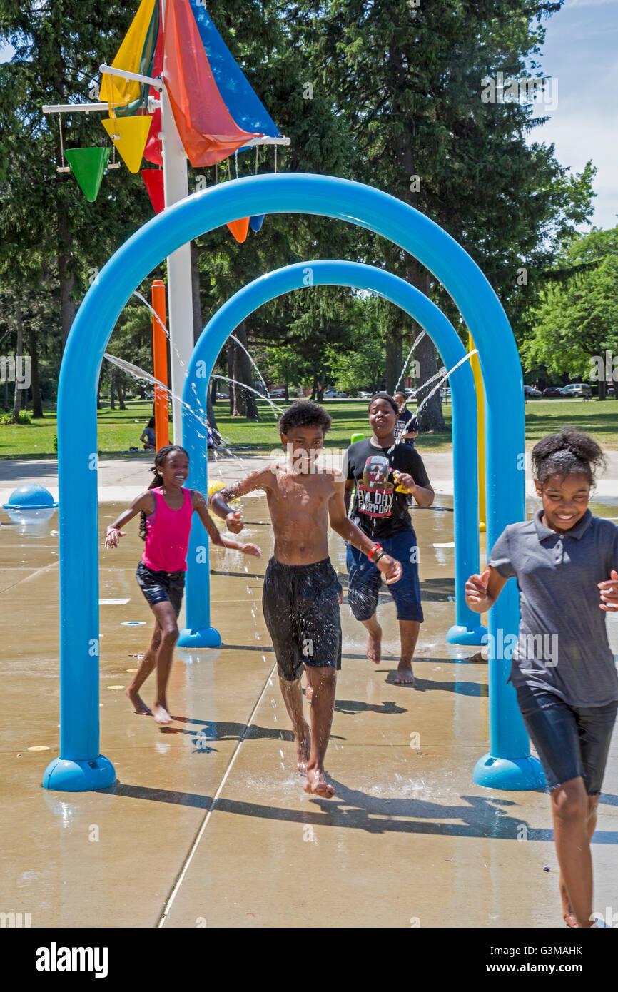 Detroit, Michigan - Children run through the water at the splash park in Palmer Park. - Stock Image