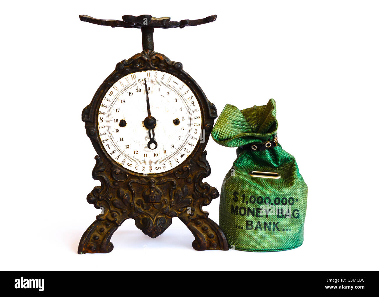 weigh the money saved in the piggy-bank with an old black cast-iron balance - Stock Image