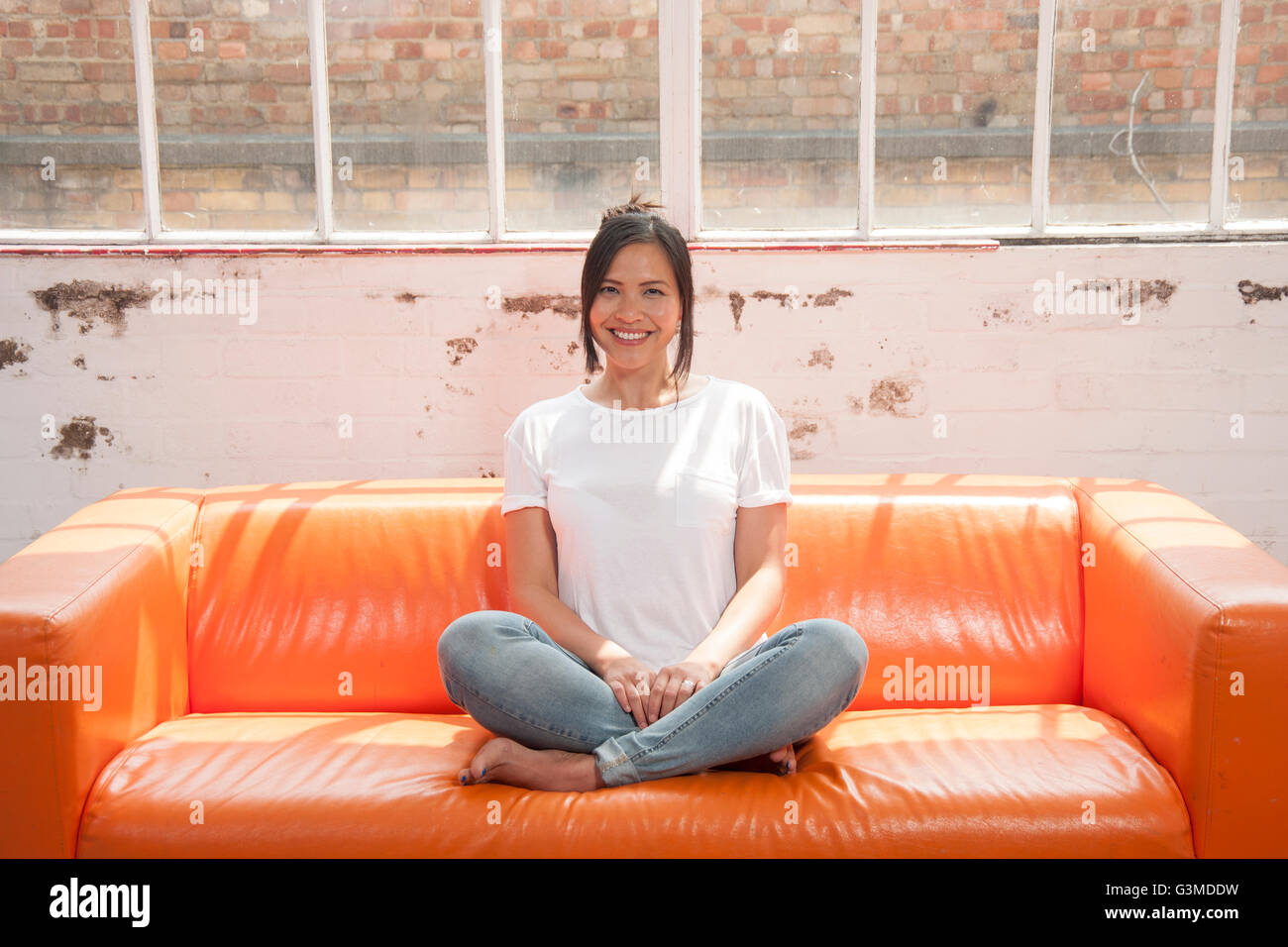 Woman sitting crossed legged on a sofa relaxing and smiling - Stock Image