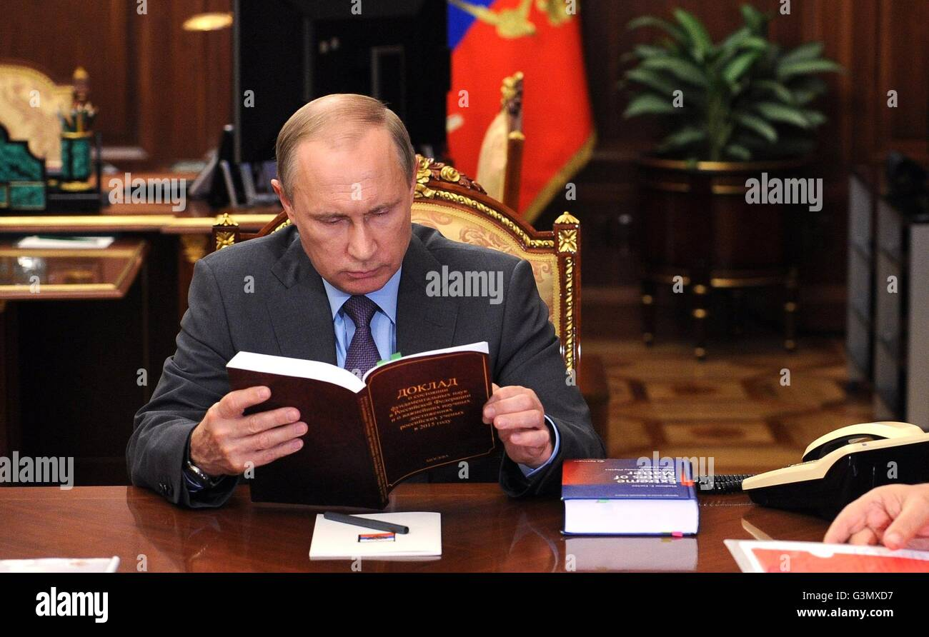 Moscow, Russia. 14th June, 2016. Russian President Vladimir Putin reviews a book during a meeting with President - Stock Image