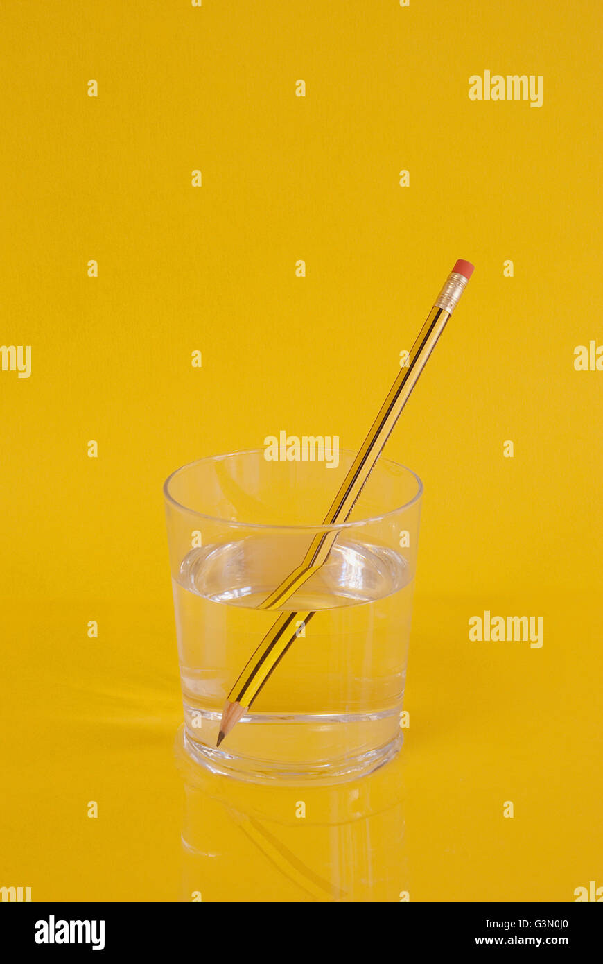 Pencil in a glass of water. - Stock Image