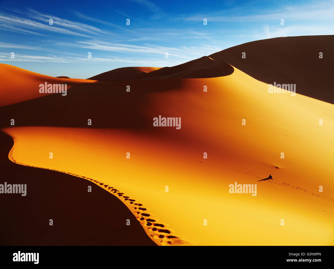 Sand dune with footprints at sunrise, Sahara Desert, Algeria - Stock Image
