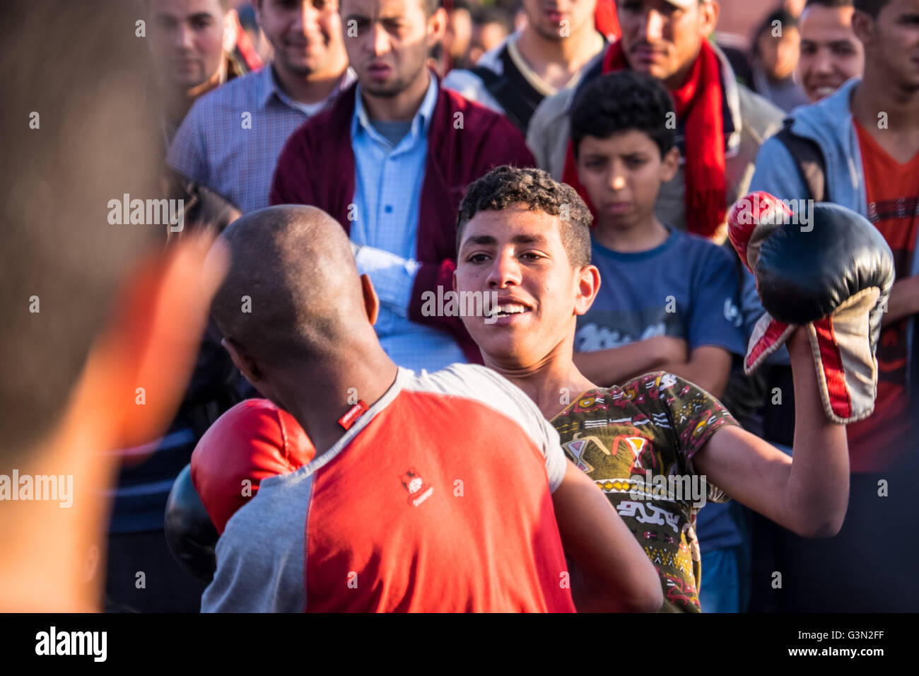 Moroccan youths boxing to entertain the crowds in Jemma el Fna, Marrakesh / Marrakech, Morocco - Stock Image