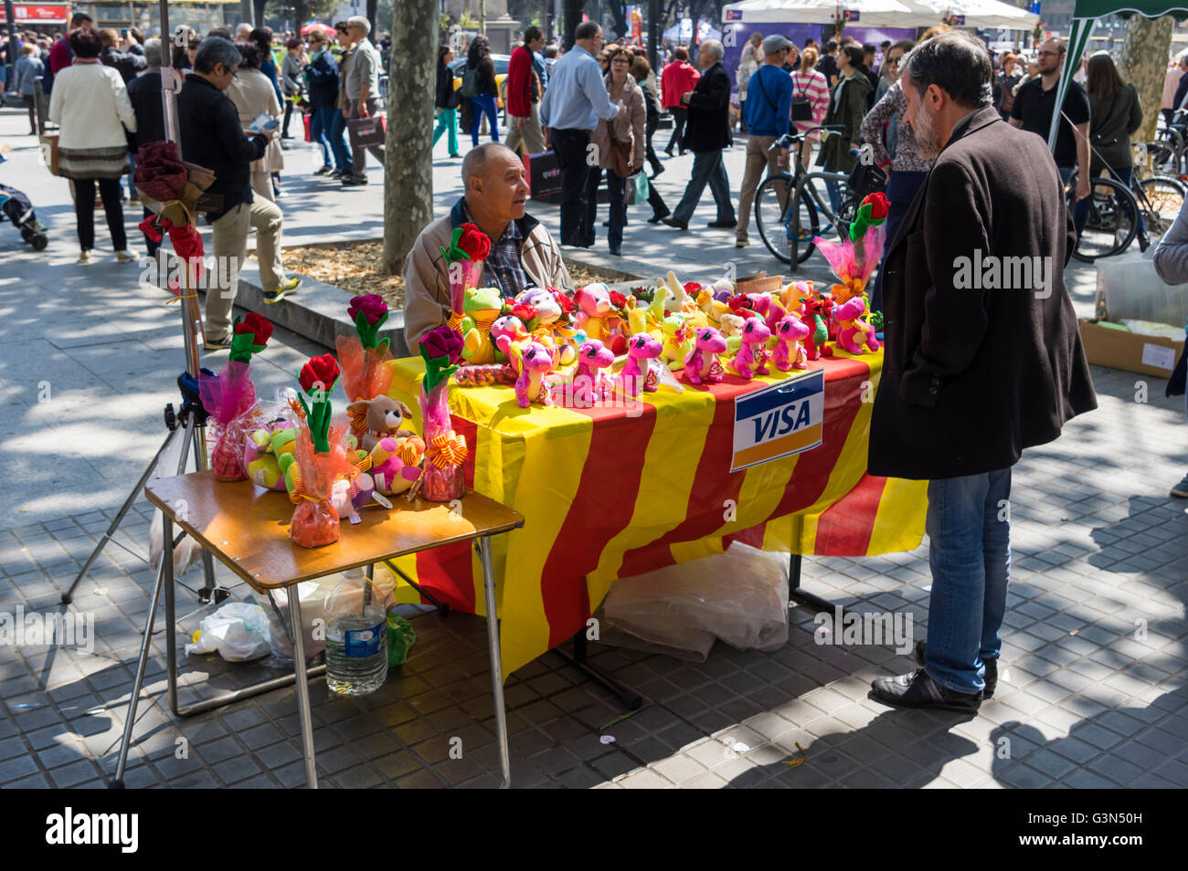 Market booth with Catalan flags selling plush dragons on Diada de Sant Jordi (Saint George's Day), 23 April, - Stock Image