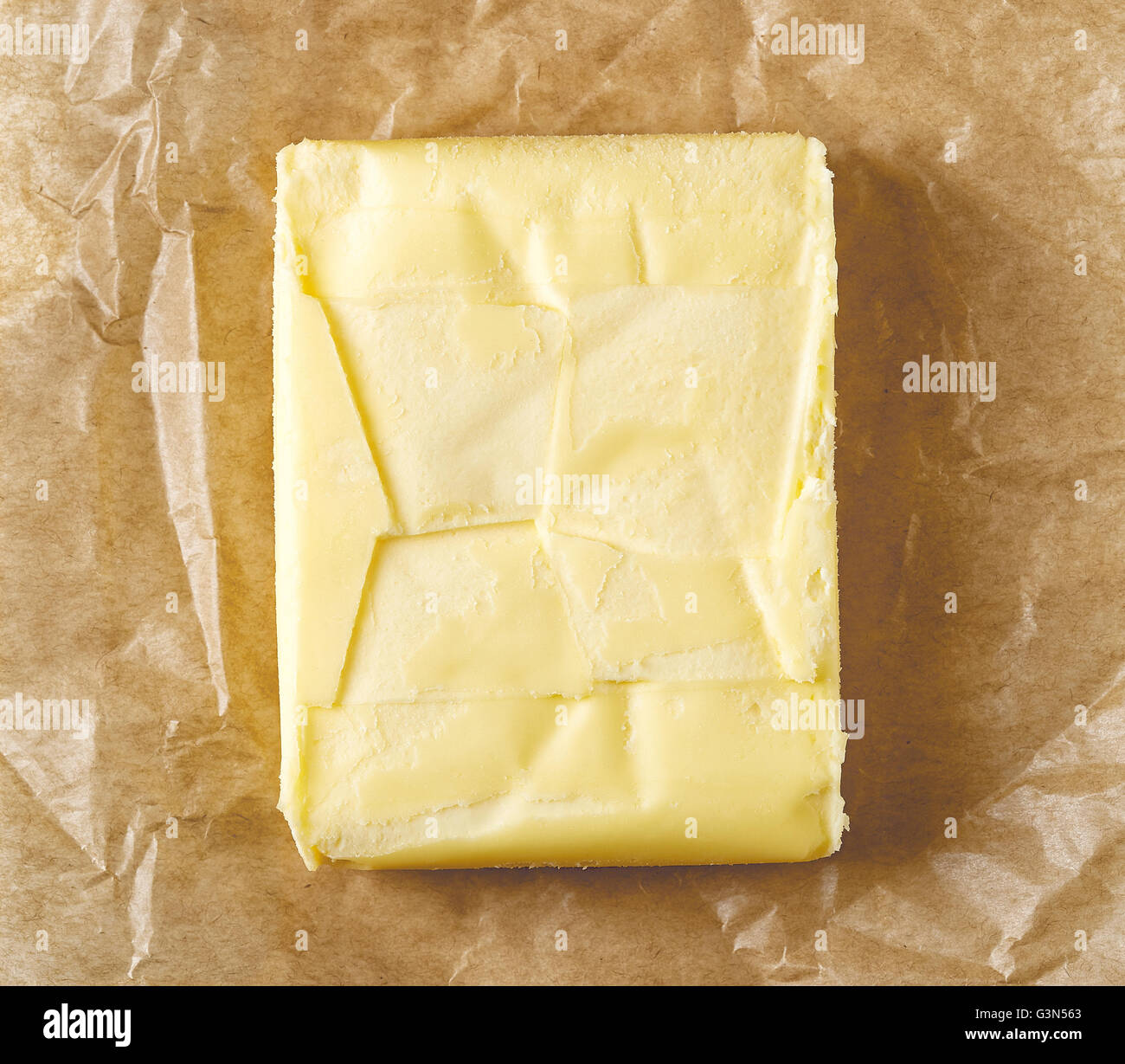 Fresh butter on pergament paper, top view - Stock Image
