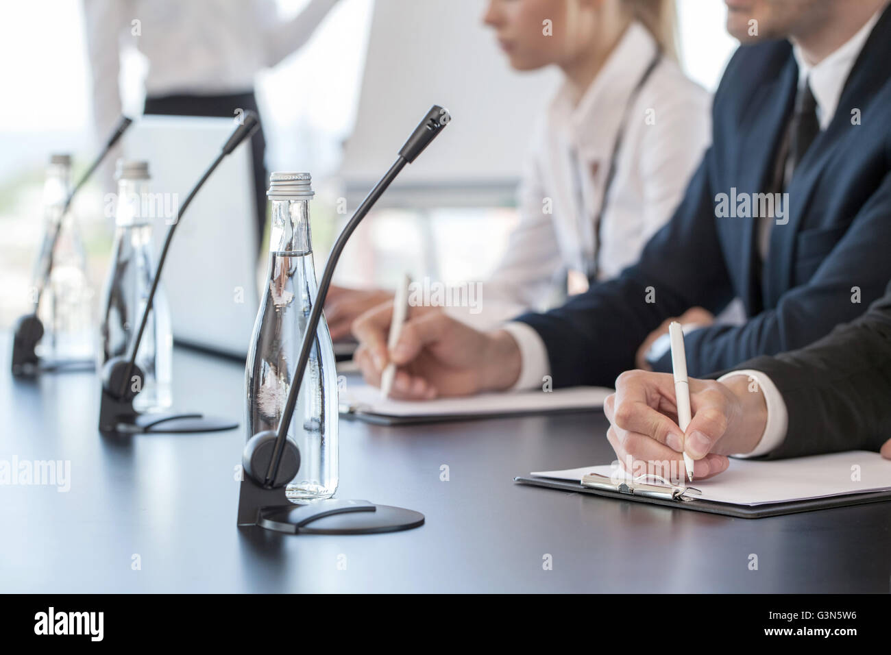 Business people speaking at presentation in microphones in office - Stock Image