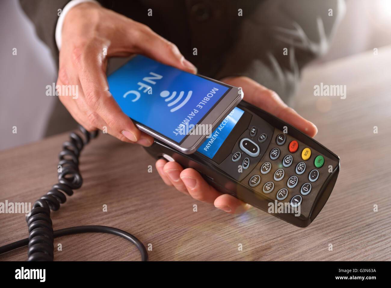 Payment on a trade through mobile and NFC technology. Front elevated view. Horizontal composition. - Stock Image