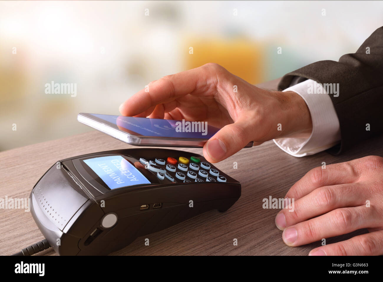 Payment on a trade through mobile and NFC technology. Elevated view. Horizontal composition. - Stock Image