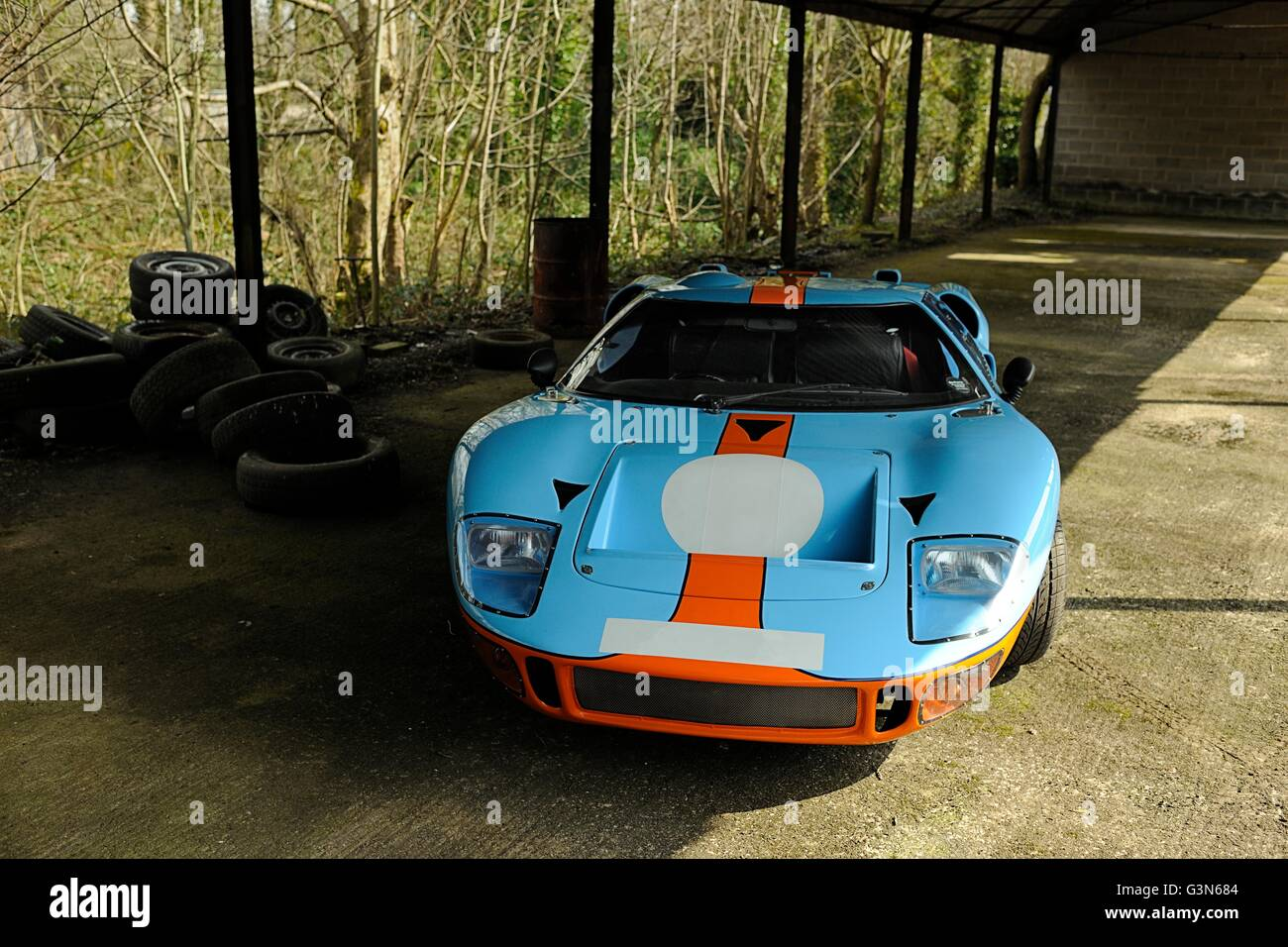 Front view of Ford GT MkII in Gulf Racing livery parked under a covered shed - Stock Image