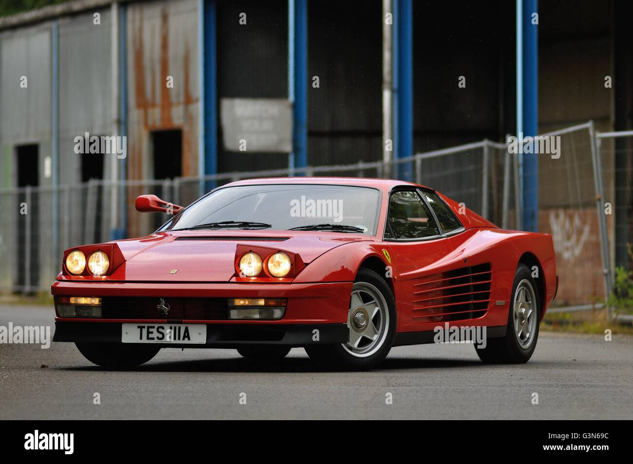 An Eighties Ferrari Testarossa stands with its headlights on in a disused industrial complex. - Stock Image