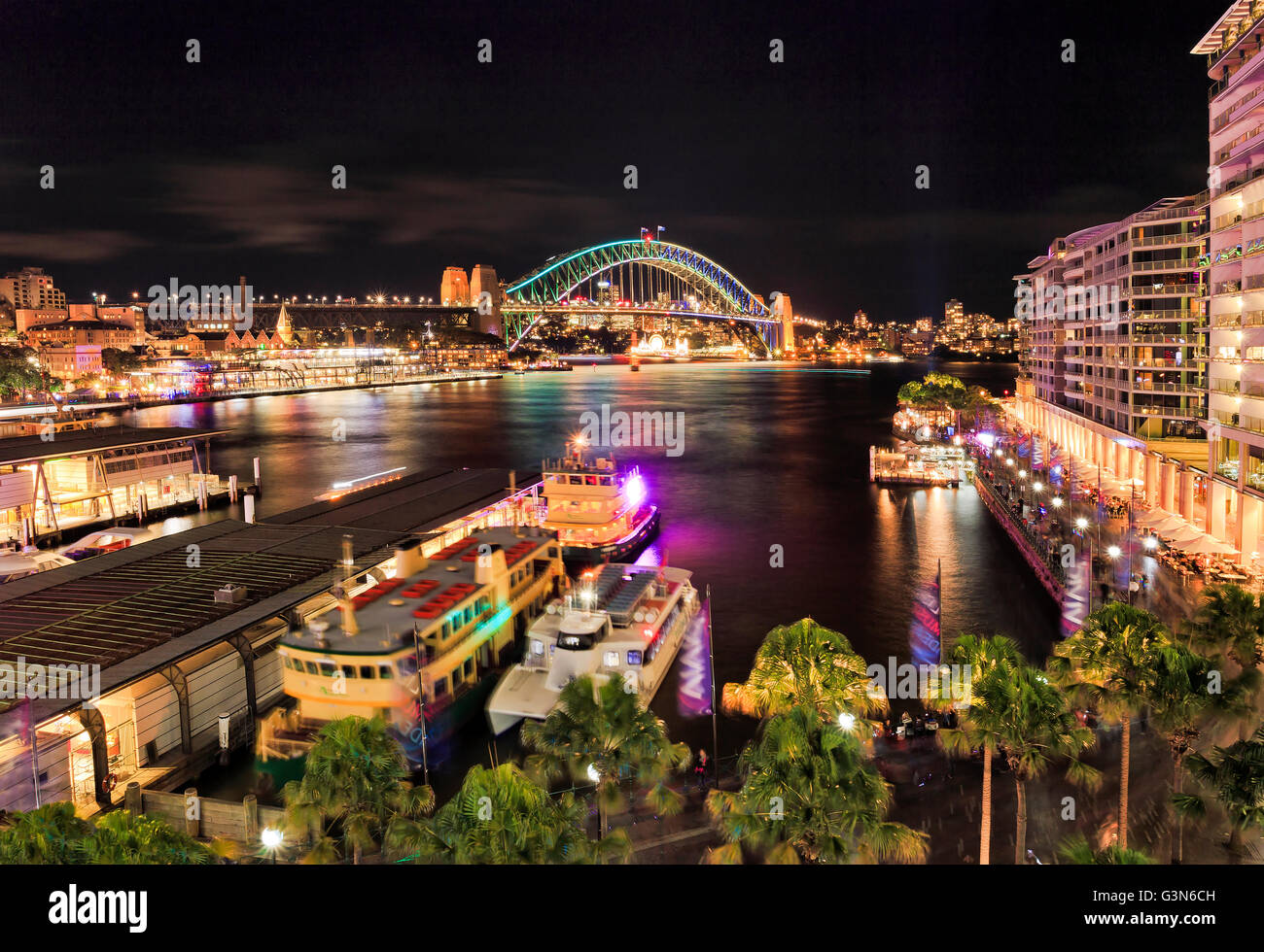 Elevated panorama of Sydney harbour circular quay bay at night during bright illumination by light towards the arch - Stock Image