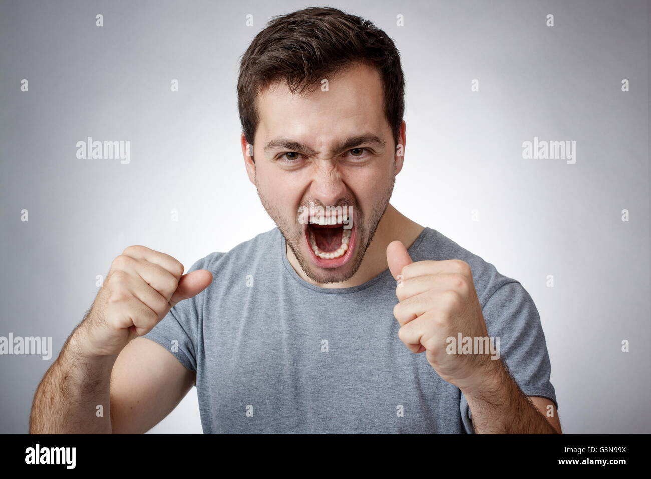 Angry young man clutching fists and shouting - Stock Image