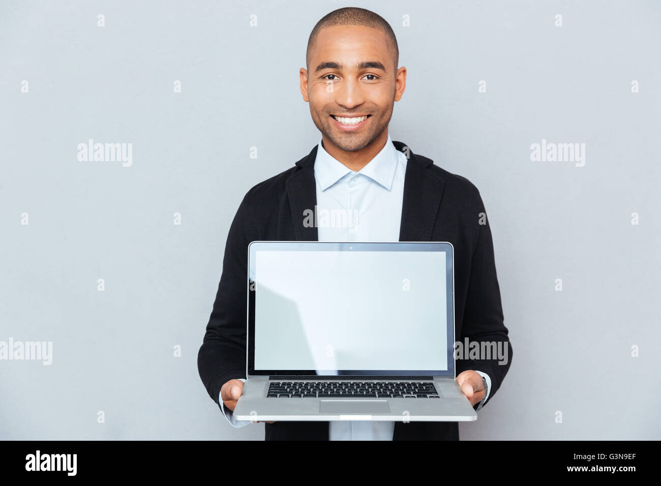 Smiling african american young man holding blank screen laptop - Stock Image