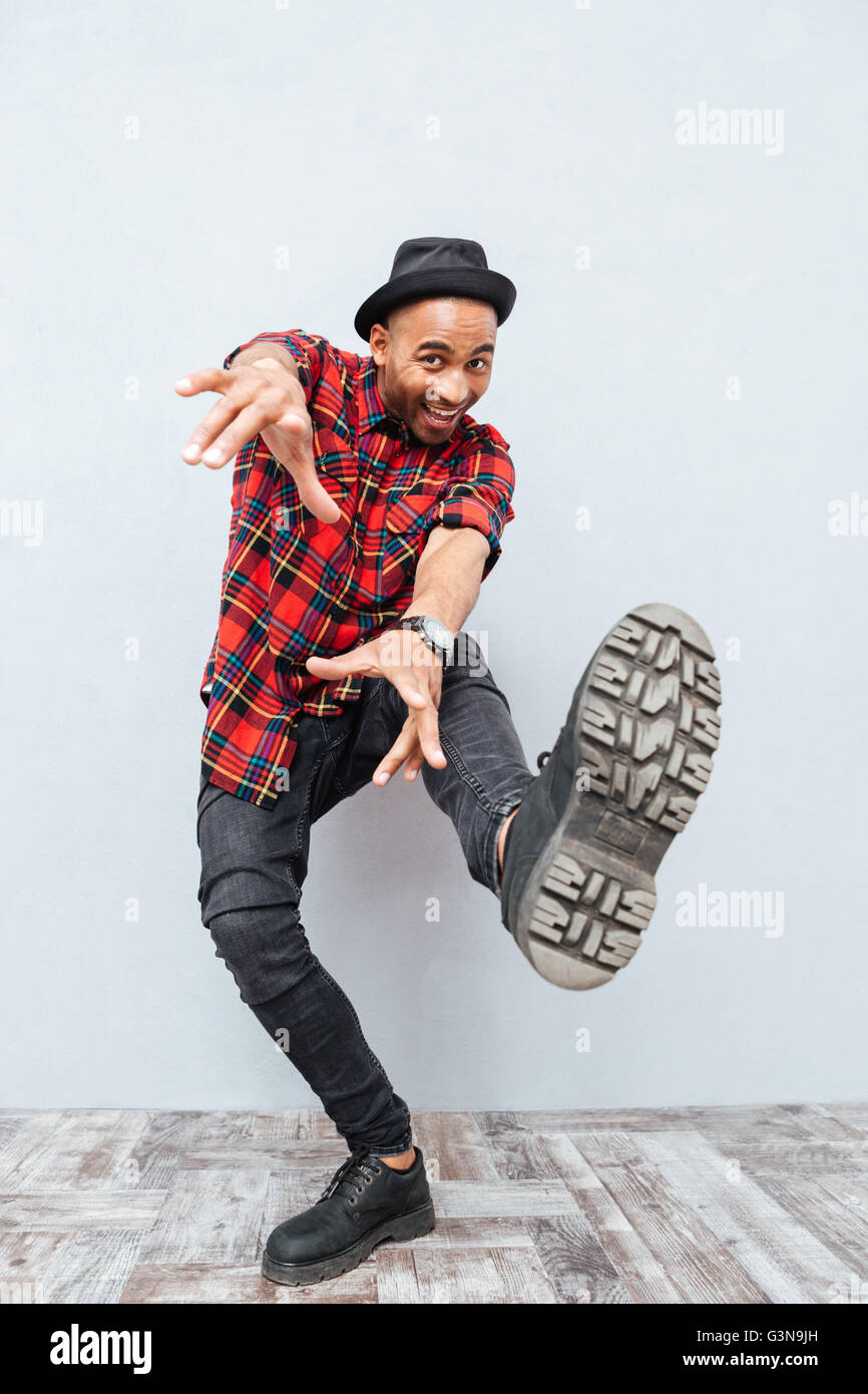 Full length of joyful african man smiling and dancing - Stock Image