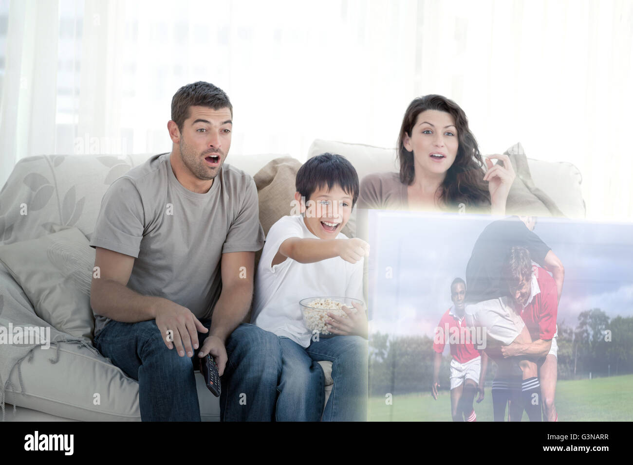 Composite image of happy family watching television - Stock Image