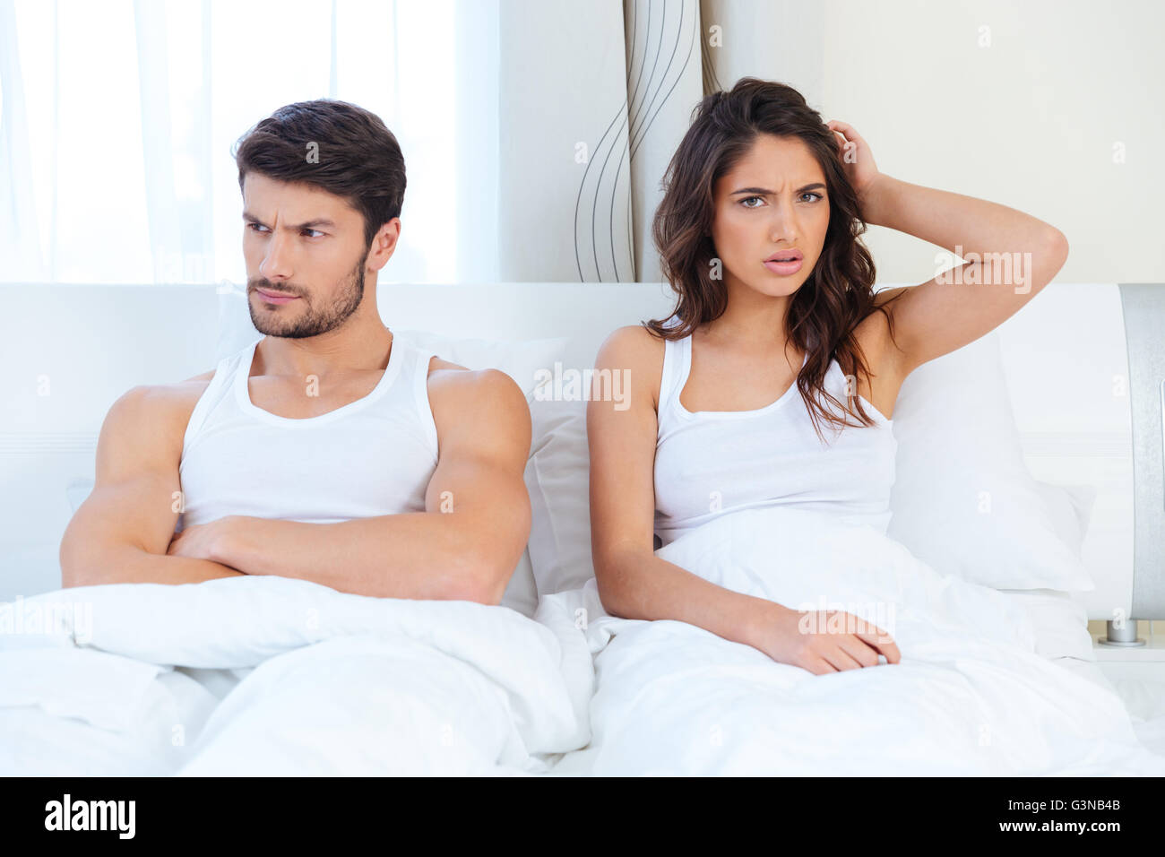 Unhappy separate couple lying in a bed at home - Stock Image