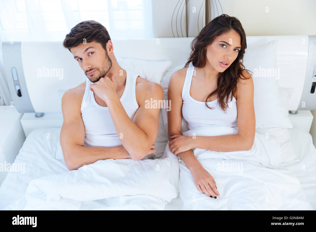 Unhappy couple not talking after an argument in bed at home - Stock Image