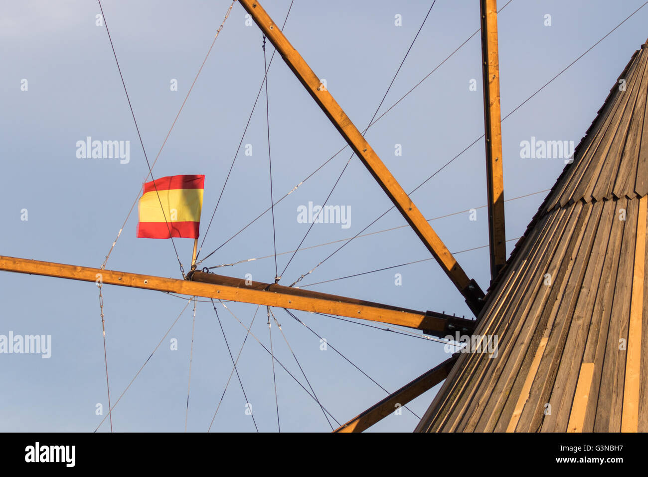 Close up of the top of an old Spanish windmill vanes, with a Spain flag and a blue sky. - Stock Image