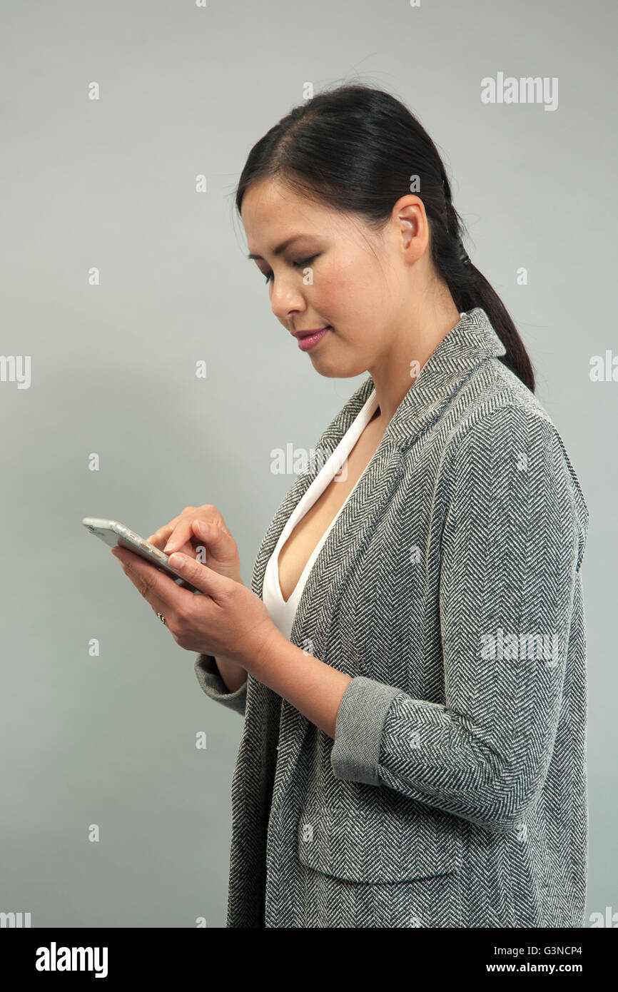 woman sending a text message on a mobile phone - Stock Image