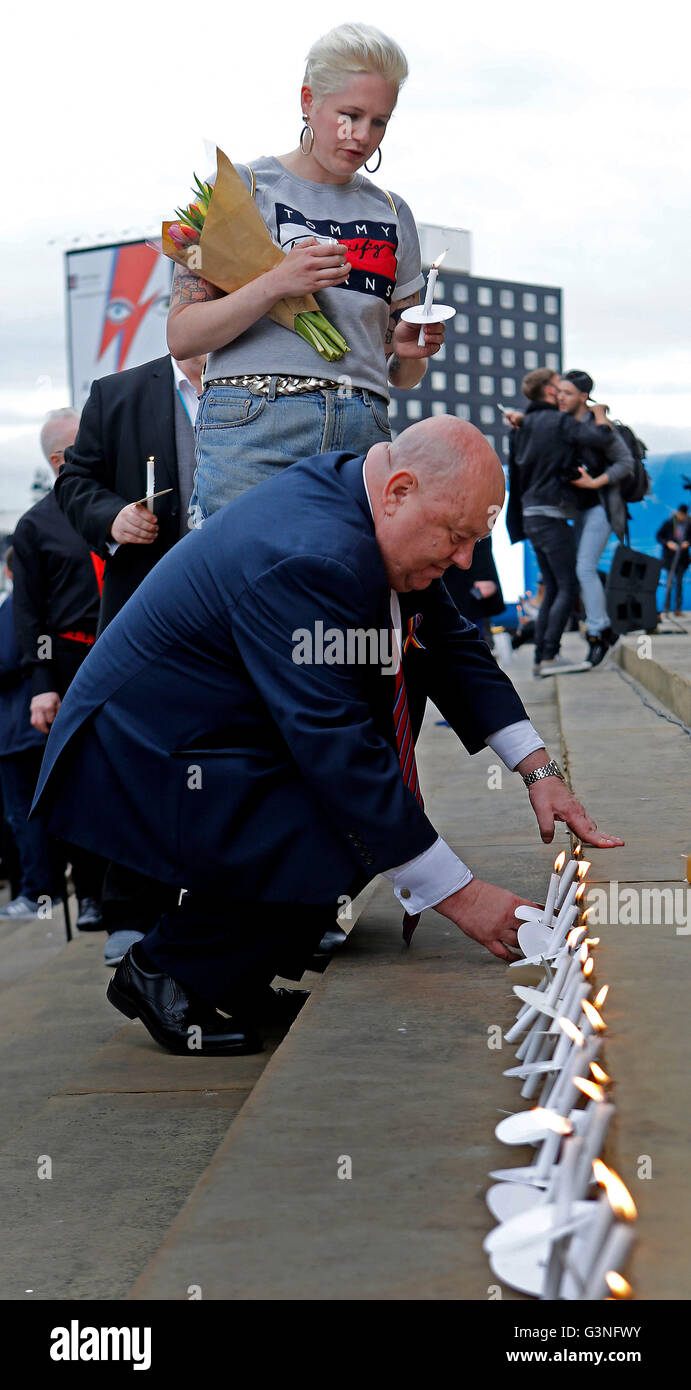 Mayor of Liverpool Joe Anderson lays a candle as he attends a vigil at St Georges Hall, Liverpool, for the victims - Stock Image