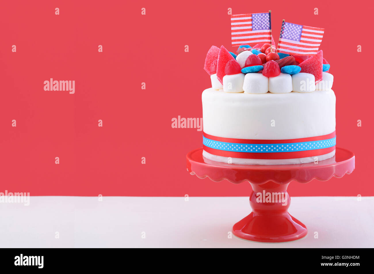 Happy Fourth Of July Celebration Cake With Flags Marshmallow And Candy Decorations On A Red Stand White Table Against