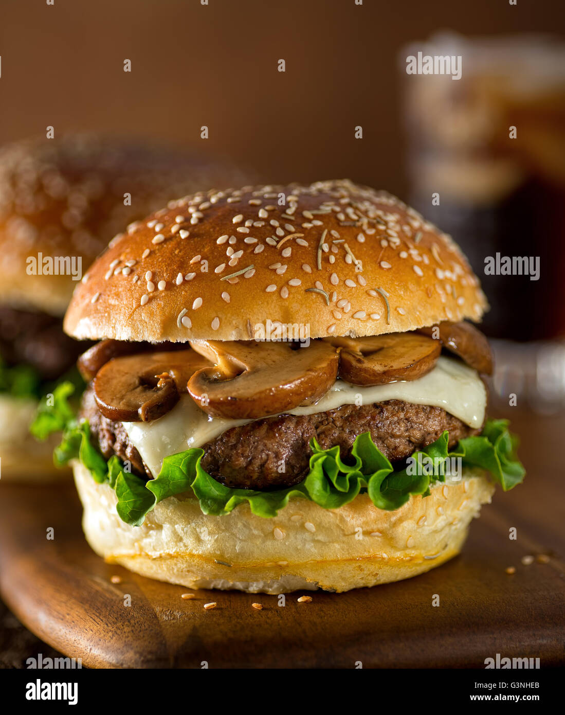 A delicious gourmet hamburger topped with swiss cheese and fried mushrooms on a rosemary sesame seed bun. - Stock Image