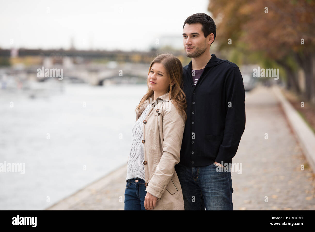 young couple man and woman standing on the riverside of Seine, Paris, France - Stock Image
