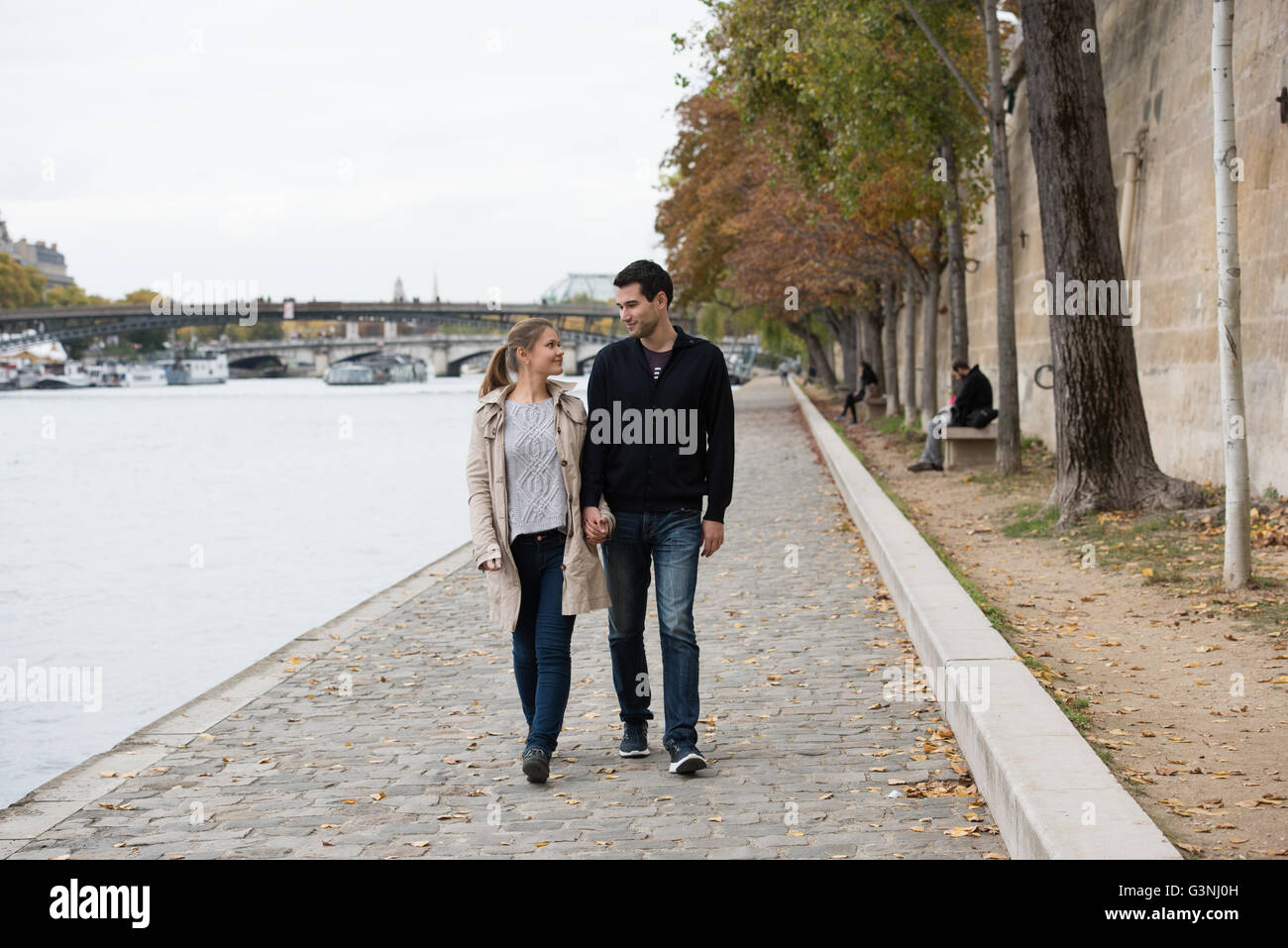 young happy couple man and woman on the riverside of Seine, Paris, France - Stock Image