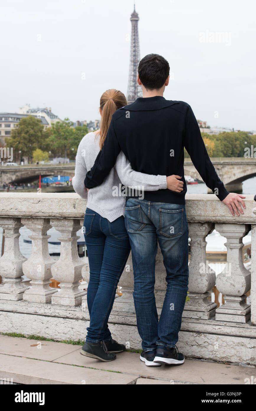 young couple man and woman standing on the bridge on river Seine, Paris, France, in front of Eiffel Tower - Stock Image