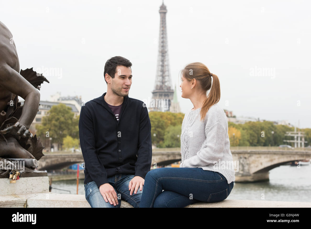 young couple man and woman sitting on the bridge on river Seine, Paris, France, in front of Eiffel Tower - Stock Image