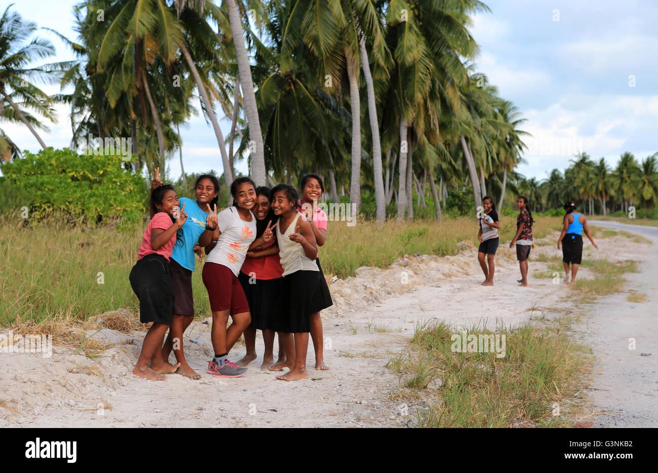 Local girls walking along the road in the evening, Christmas Island, Kiribati - Stock Image