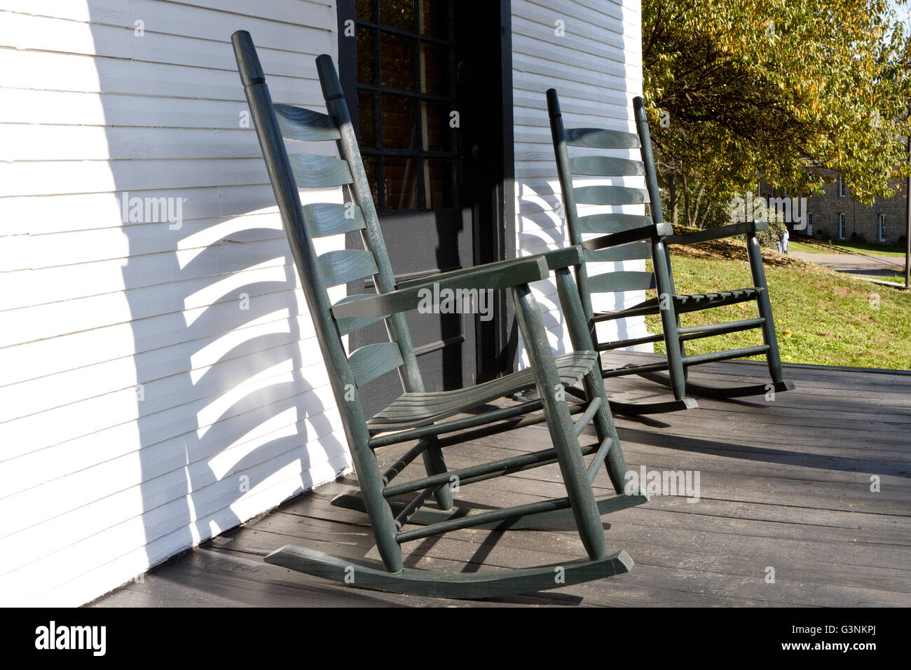 Traditional wood rocking chairs on the front porch - Stock Image