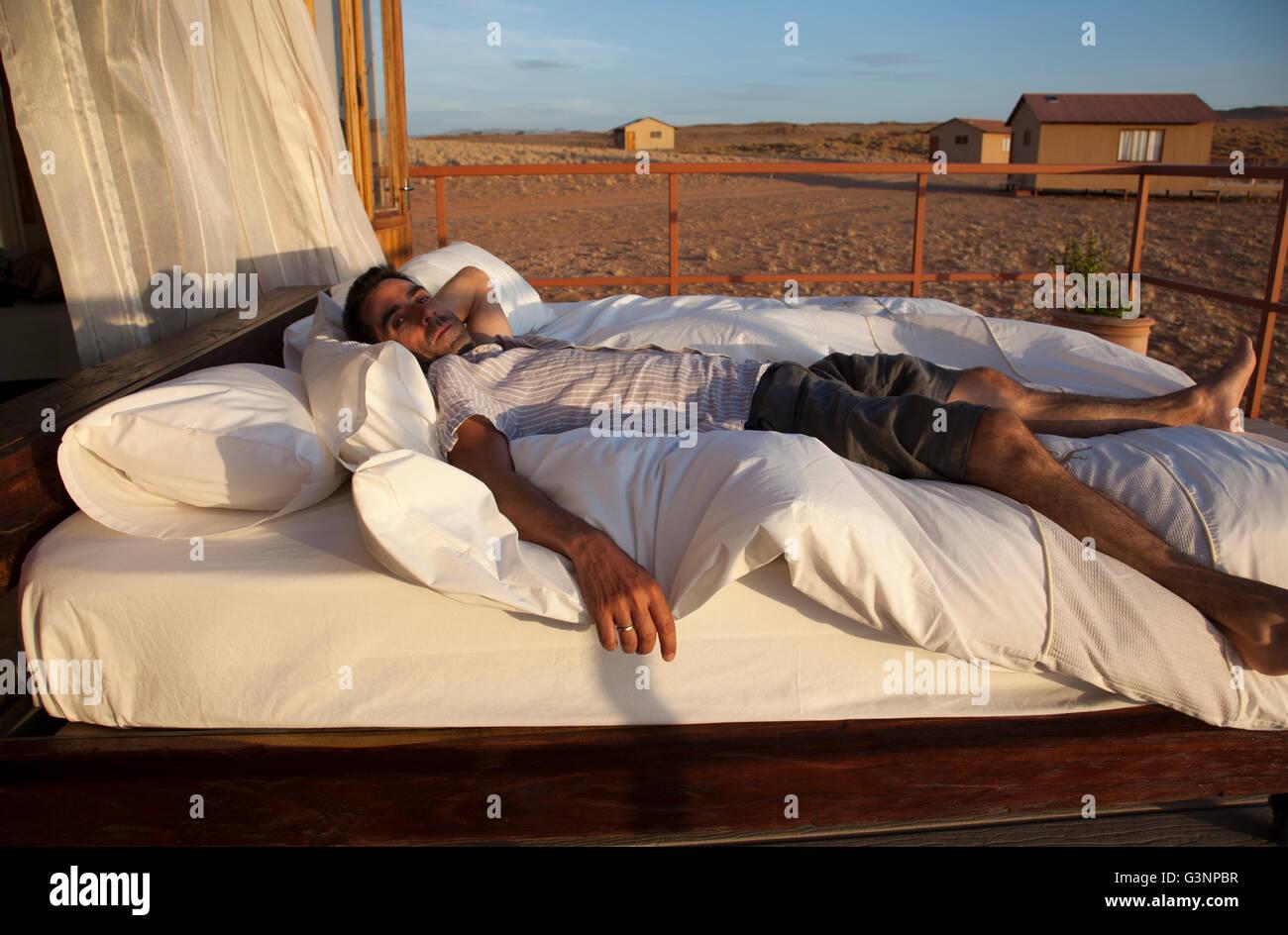 Man on Bed at Namib Desert Star Dune Camp in Namibia - Stock Image