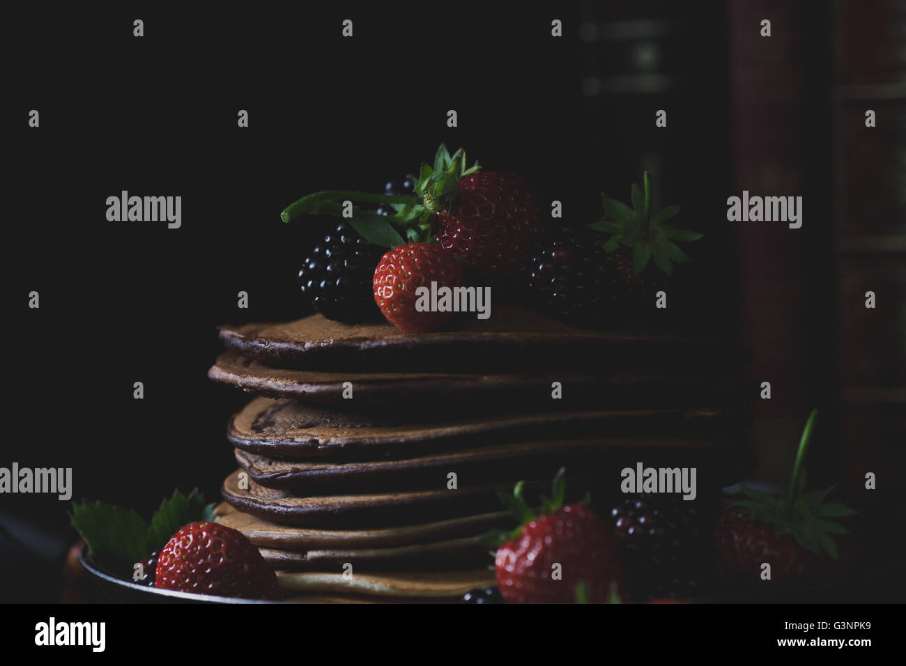 Pancakes in the rusty pan with strawberries and blackberries  and old books in background with mystical light - Stock Image