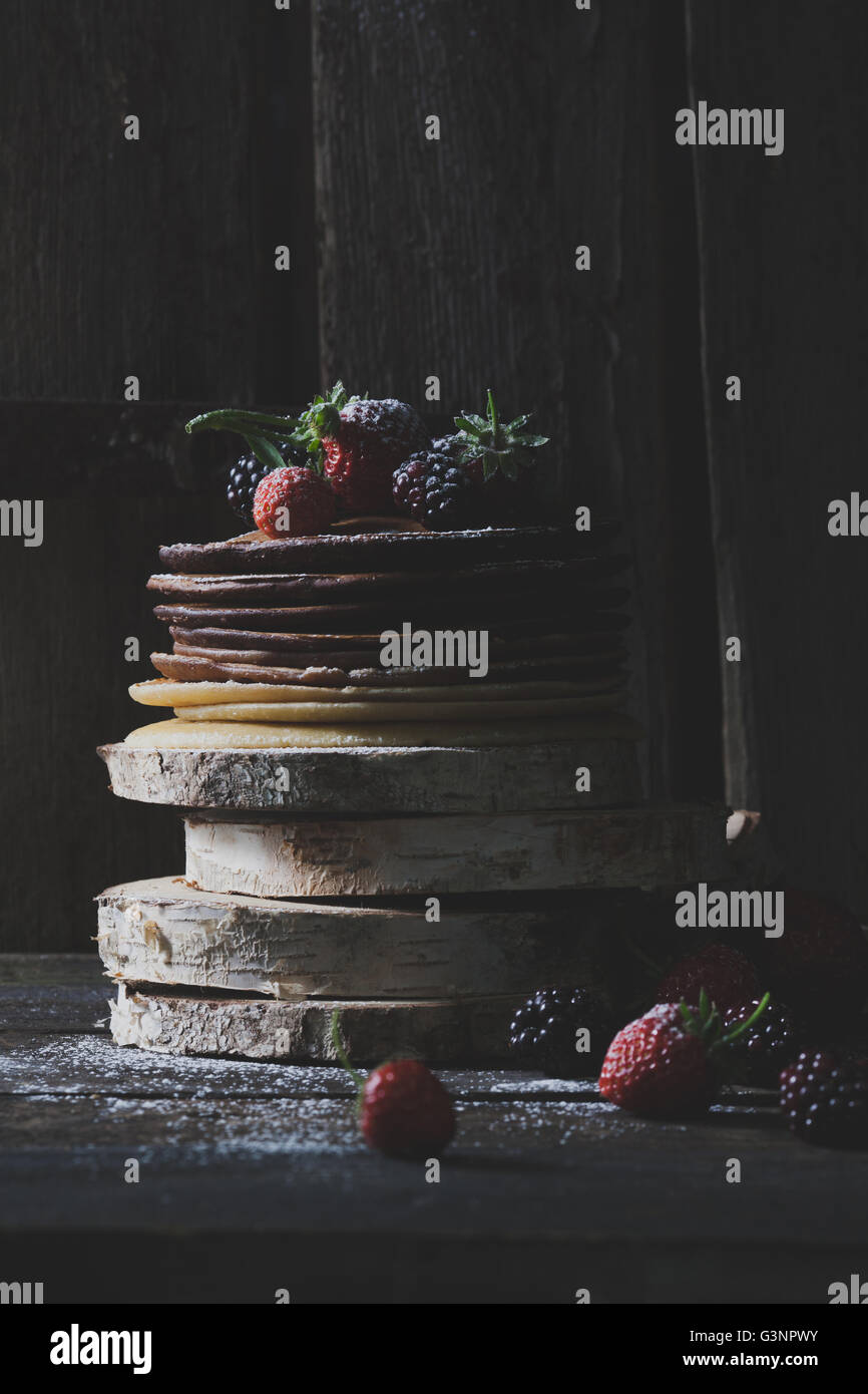 Rustic pancakes with organic fruits on wooden blocks with old wooden doors in backround Stock Photo