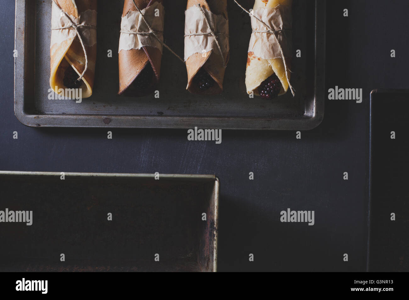Pancakes with blackberries on rusty tinwere with silver knife and fork on scratched blackboard with baking trays - Stock Image