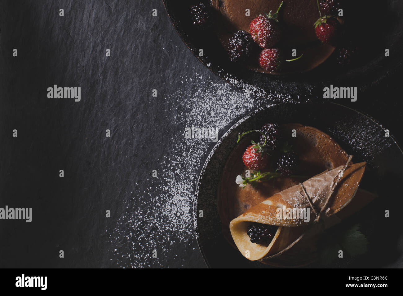 Chocolate pancakes on rusty pans lying on dark stone with beautiful light, flat lay - Stock Image