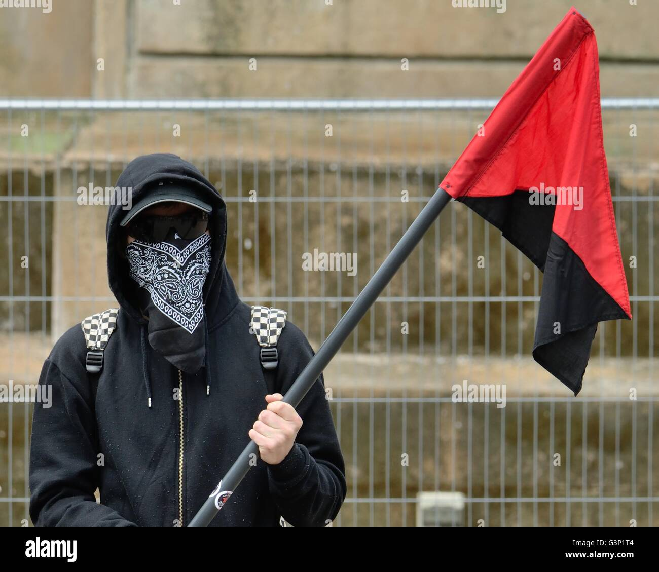 A youth with his face covered hold a diagonally bisected red and black flag of the anarchist movement. - Stock Image