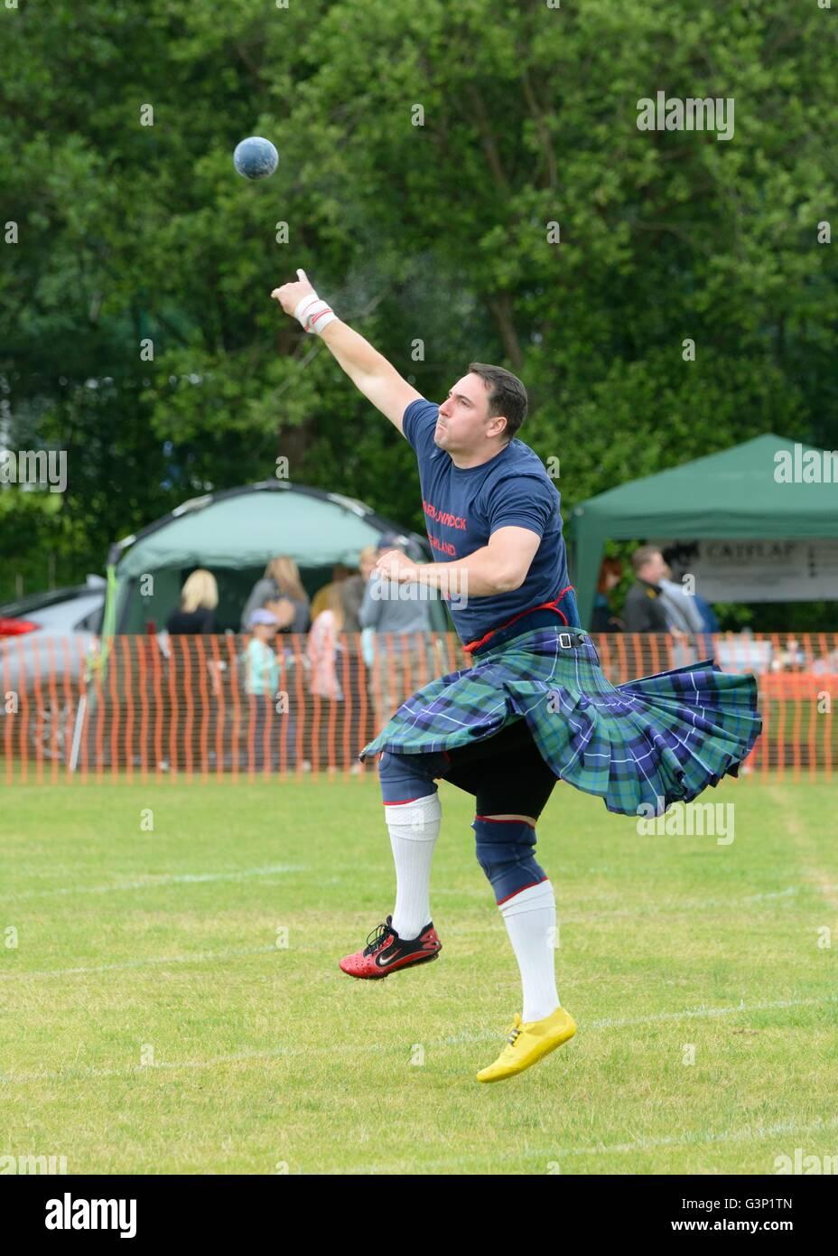 Man in kilt shot putting at Highland Games, Scotland, UK - Stock Image