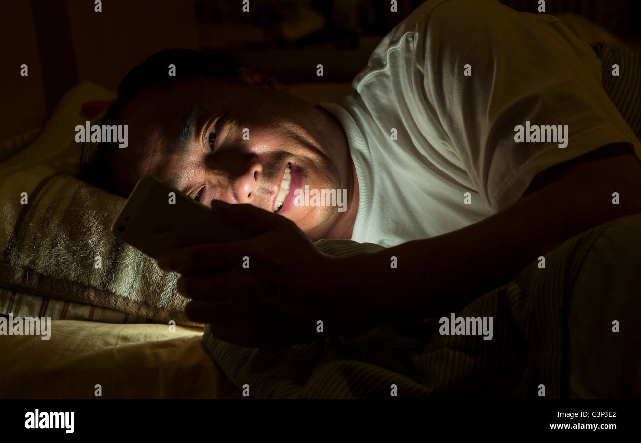 A man text messaging at night on a bed - Stock Image