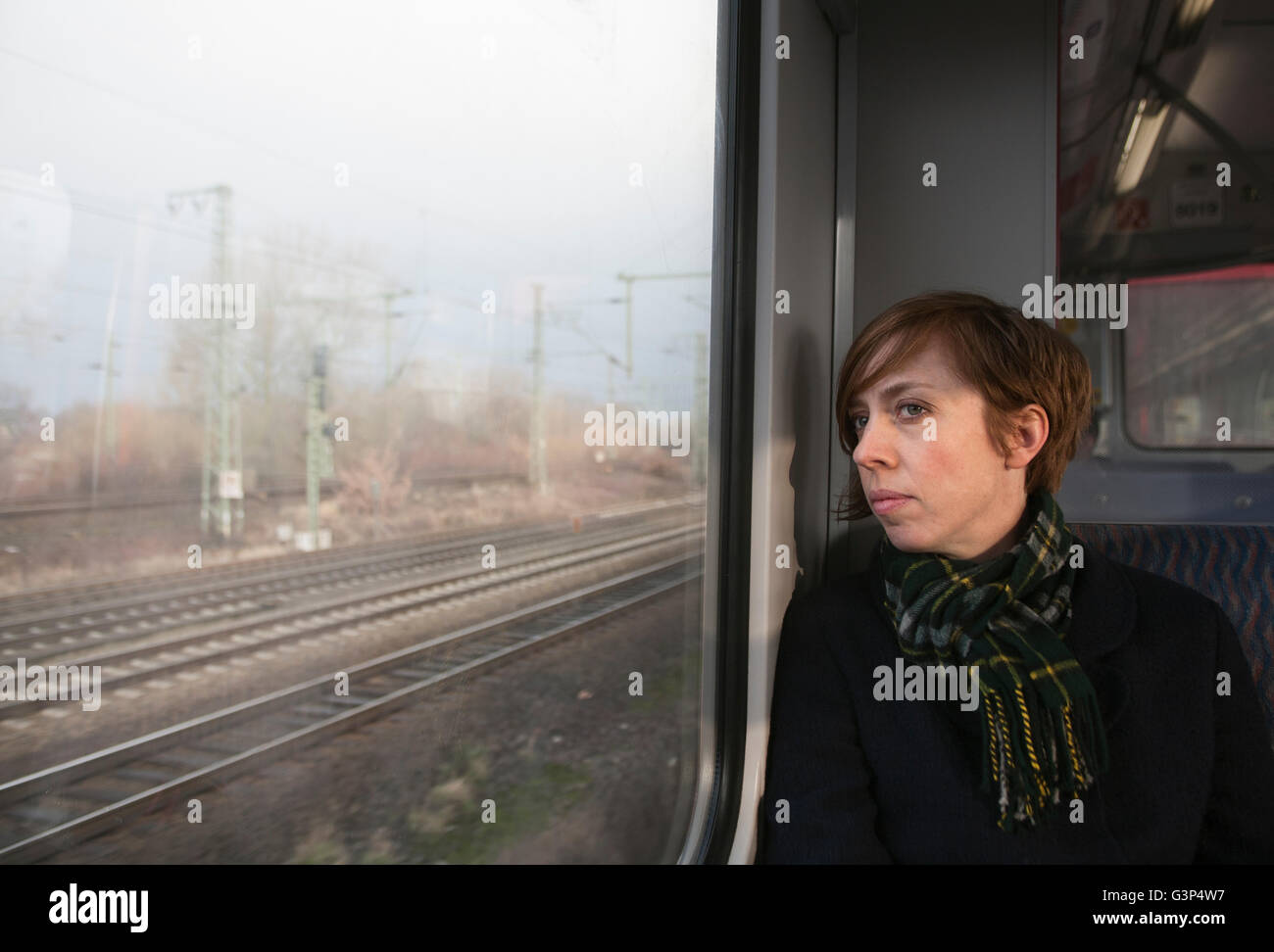 Germany, Mid adult woman on train looking through window - Stock Image