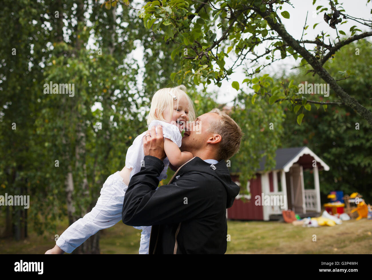 Sweden, Uppland, Father holding up daughter (4-5) - Stock Image