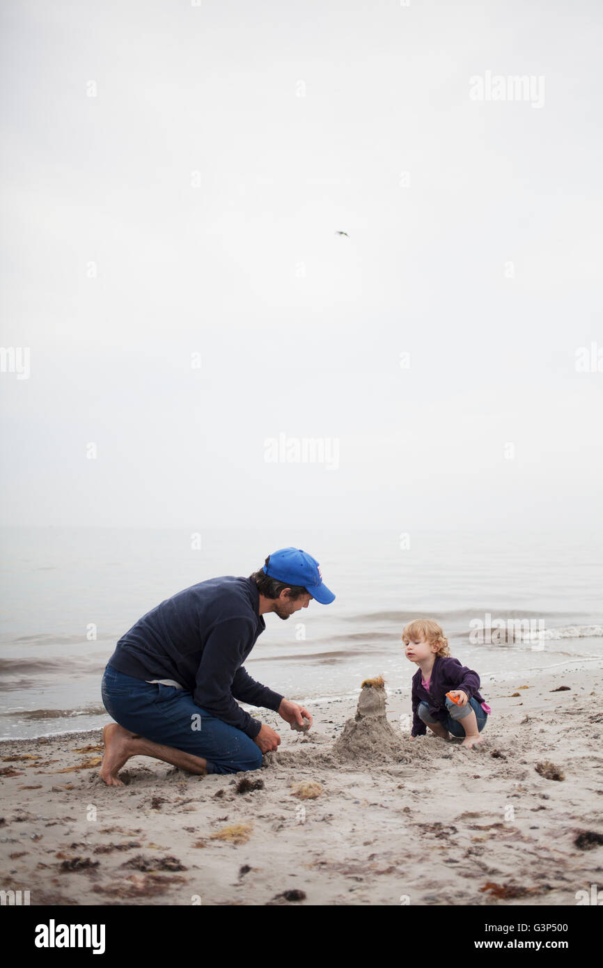 Sweden, Skane, Osterlen, Dad building sand castle with his daughter (2-3) - Stock Image