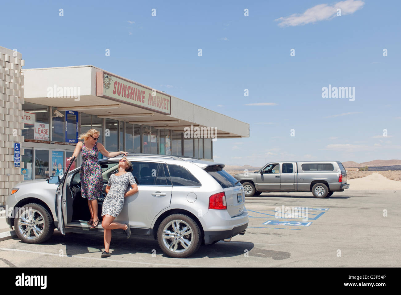 USA, California, Female friends on road trip in front of market - Stock Image