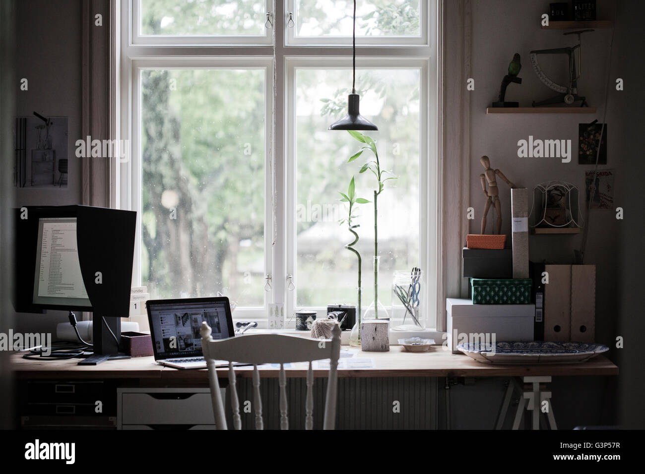 Sweden, Desk with laptop and computer monitor by window - Stock Image