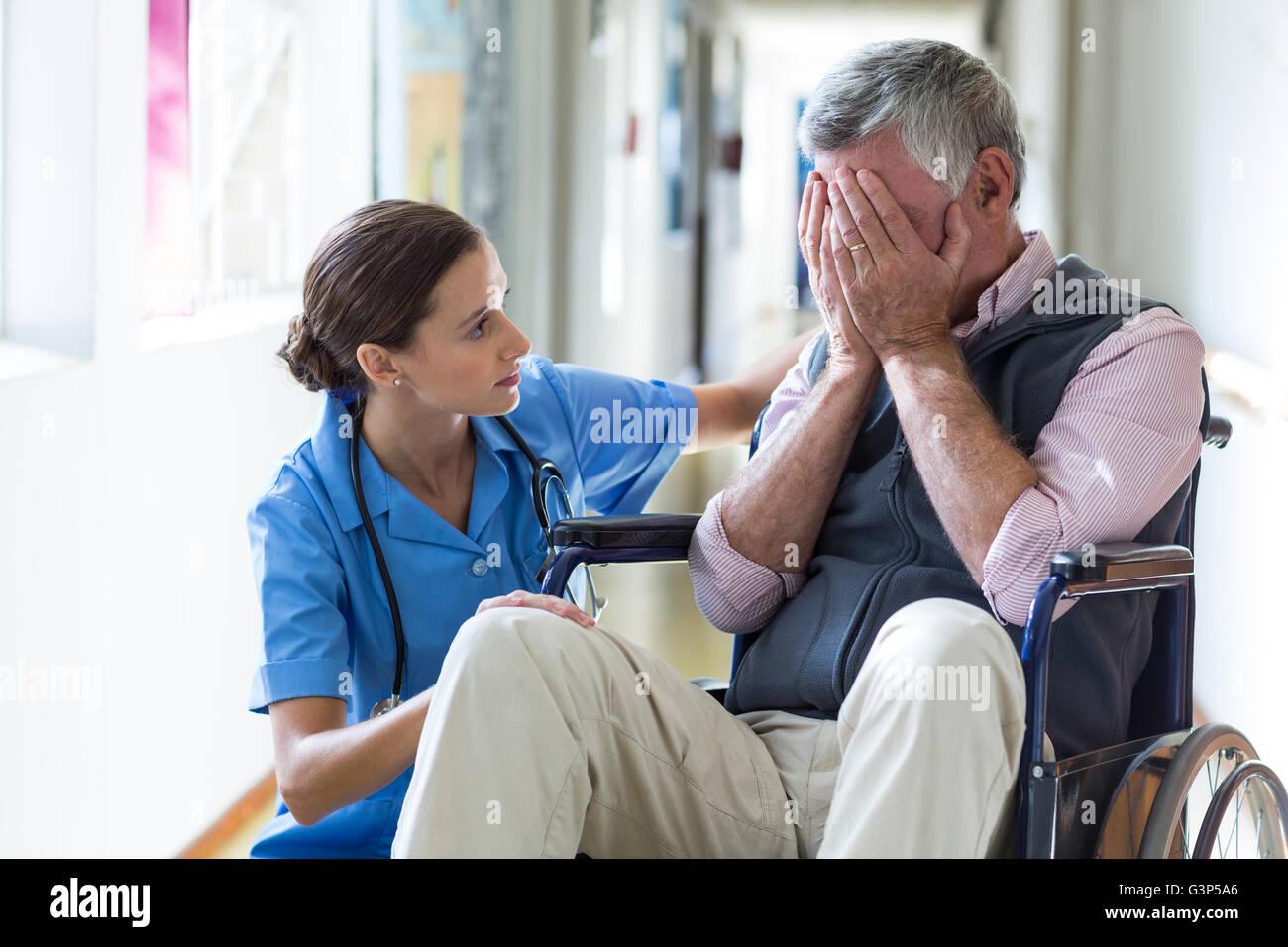 Female doctor consoling senior man in corridor - Stock Image