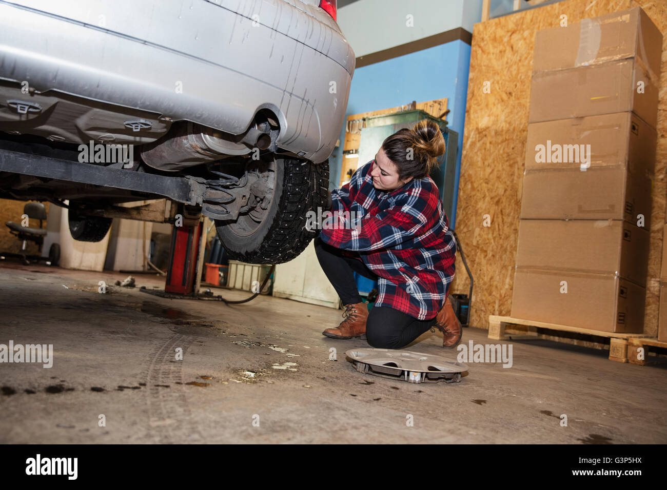 Sweden, Female mechanic adjusting wheel - Stock Image