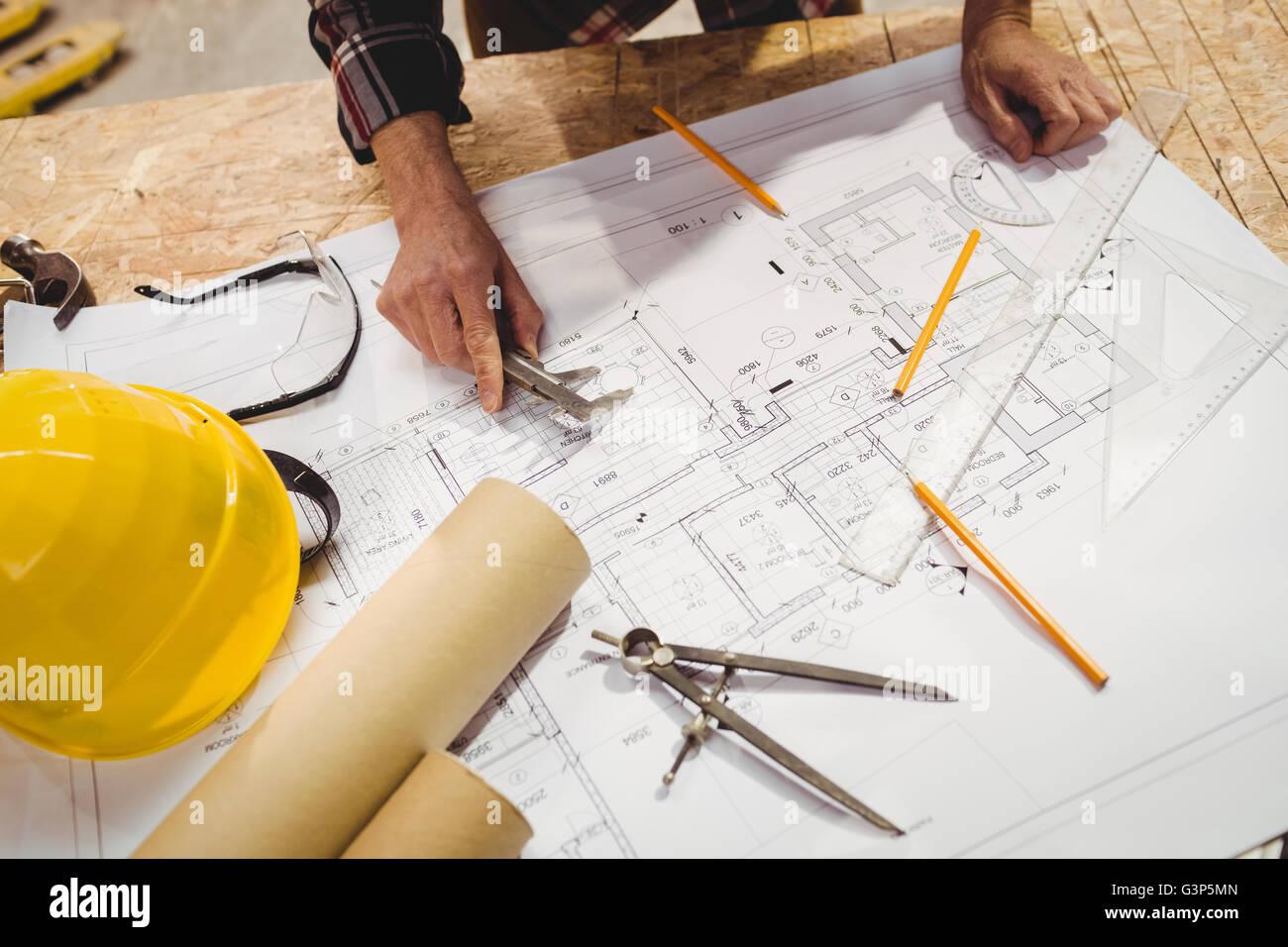 Carpenter taking measures on a plan - Stock Image